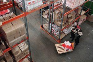Photo de deux personnes dans un entrepôts qui travaillent