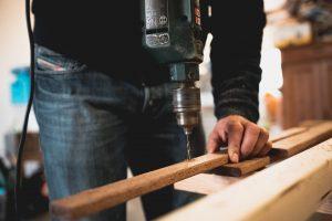 Photo d'une personne faisant un trou au foret dans une planche de bois