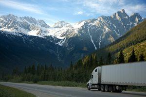 Photo d'un camion sur la route avec des montagnes en fond